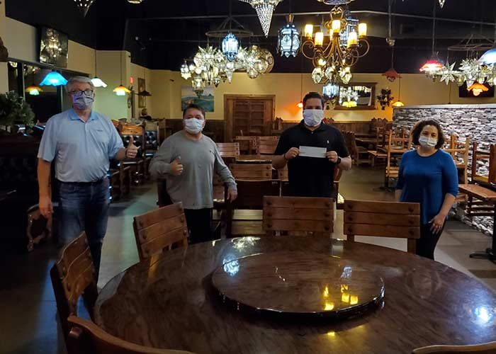 Bankers and restaurant owner wearing masks and completing loan documentation