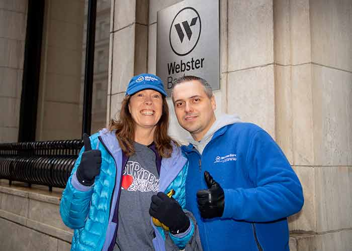Two people stand outside Webster Bank giving a thumbs up