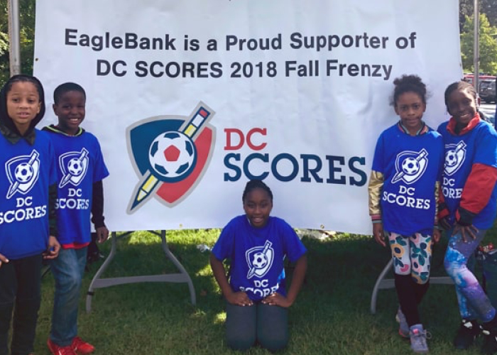 A youth soccer team poses in front of an Eagle Bank sponsorship banner