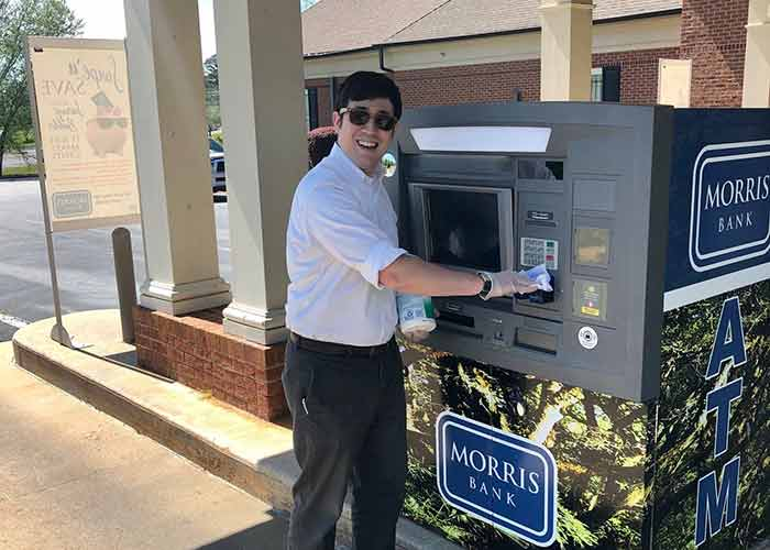 Bank employee sanitizing an ATM