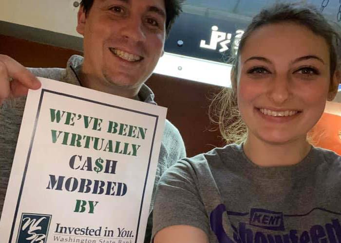 Two people hold up a sign that got them $15 off a meal at a local restaurant