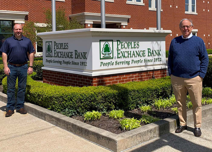 Two bankers stand around a sign for Peoples Exchange Bank