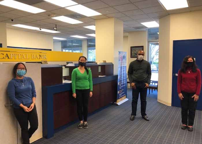 Bank employees wearing masks and standing socially distant