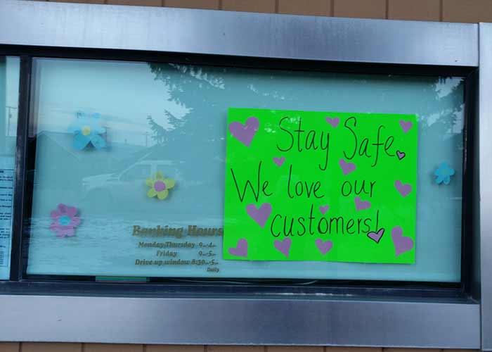 "Bank drive-thru window with a sign that says, ""Stay safe! We love our customers!"""