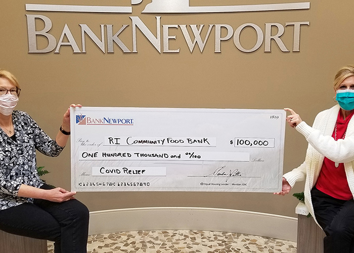 Two bank employees hold an oversized check to the Rhode Island Community Food Bank